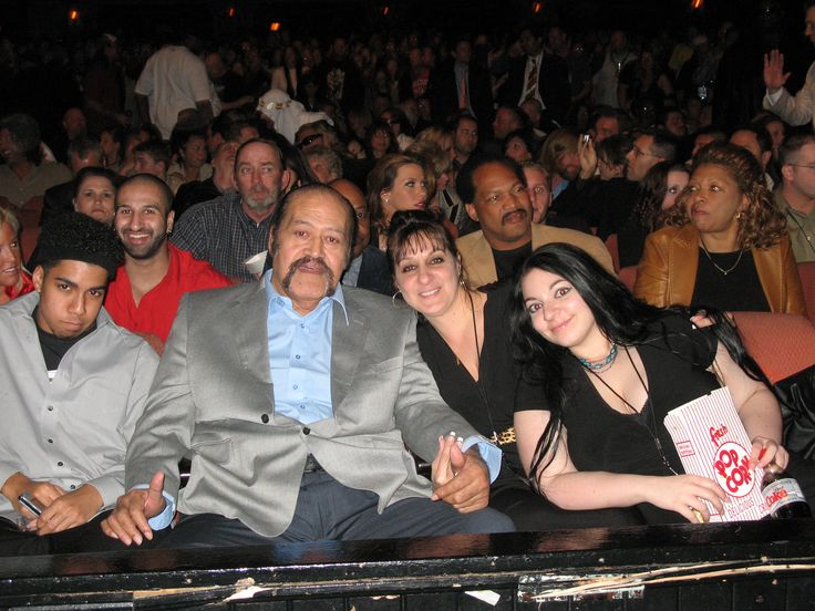 Afa Anoa'i, his wife Lynn, & their daughter Tovale. Other wrestlers can be seen in the background including Ron Simmons, Teddy Long, Kenny Dykstra, Mickie James, Shawn Divari, Triple H, Sabu, & Rob Van Dam.