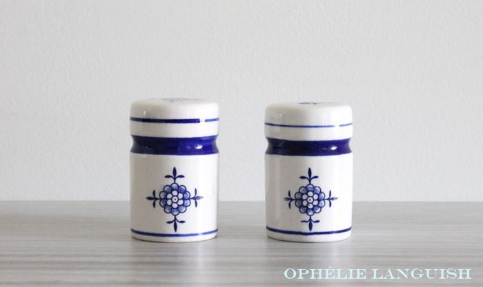 Charming set of Delft style white and cobalt blue salt and pepper shakers. Flower motif on top and sides of shakers. Cylindrical with cobalt blue banding. Plastic plug bottoms.