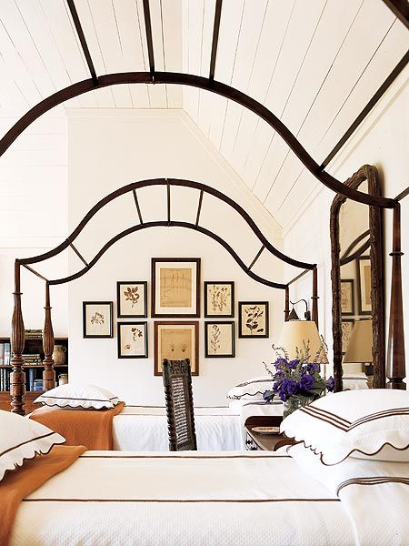 Two beds in white linens, framed prints on back wall.