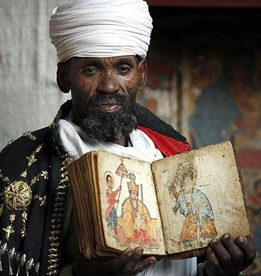 Christian Orthodox priest with an ancient painted Bible