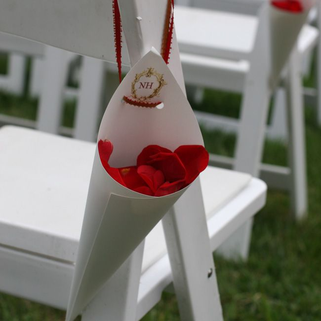 Add a little cone of rose petals to the back of each chair. On the way out of your ceremony, you will be showered in petals!