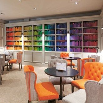 Multicoloured bookshelves and plump armchairs make for a cosy feel in the lounge of Bistro du Vin in London's Soho.