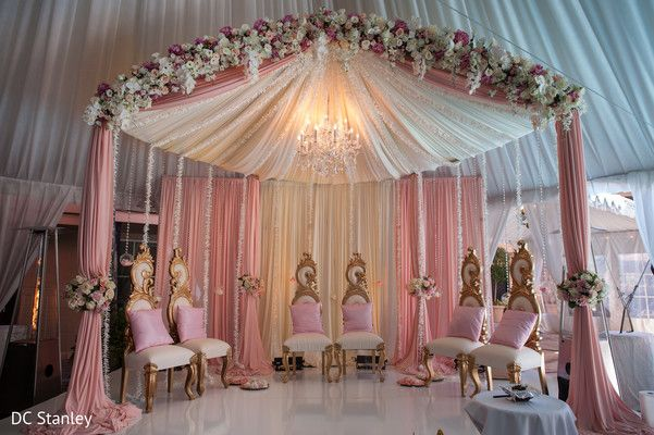 Very cool example of a mandap that is open in front so that it doesn't block the view of guests with big pillars in front, but still keeps the canopied feel on the top. Don't want pink or chandelier, probably would not do as many flowers, but like the draping style and the cream.