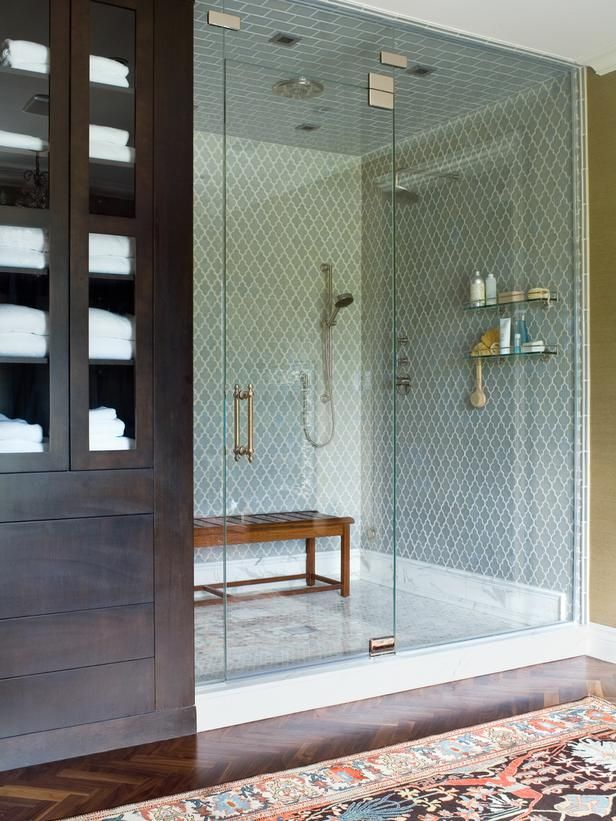 Moroccan tiles in the shower, the bench, the herringbone patterned wood floors and the rug! Exotic, modern, spa bathroom.