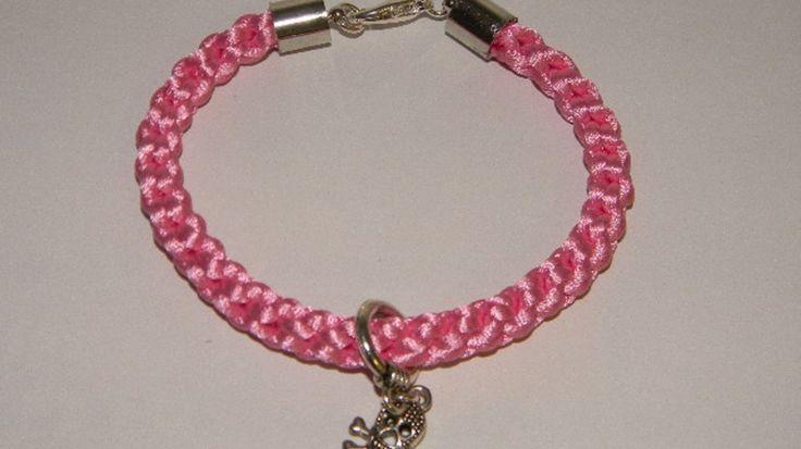 Gevlochten Kumihimo armbandIn de Japanse Kumihimo stijl gevlochten armband van roze katoensatijn met doodskop bedeltje. De uiteinden zijn afgewerkt met eindkapjes en een karabijnsluiting. Lengte:23cm.