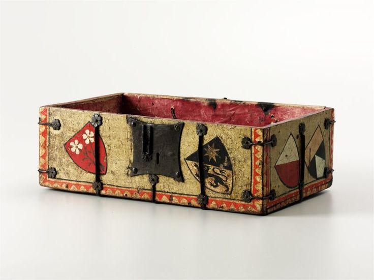 Kassette  Schriften-oder Schmuckkassette, deren Innenseite mit rot gefärbtem Leder ausgekleidet ist. Wohl 1300 - 1350. 12,7 x 39 x 23,5 cm (Kassettenteil). Korpus: Holz, massiv, bemalt. Innenfutter: Leder, gefärbt. Metallteile: Schmiedeeisen.