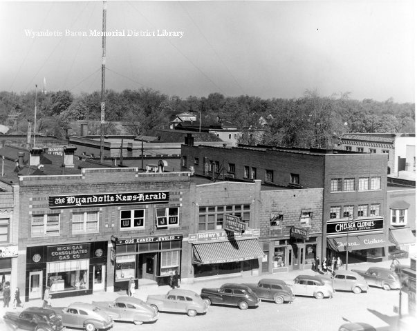 Downtown Wyandotte from top of Sears Roebuck. The west side of First Street between Elm and Maple is pictured. Michigan Consolidated Gas Company, Gus Emmert Jeweler, Wyandotte News Herald, Raido Station W. J. J. W., Harry's Funriture, Wyandotte Lunch, Chelsea Clothes. About 1948.
