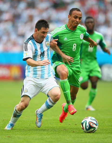 Lionel Messi of Argentina is challenged by Peter Odemwingie of Nigeria during the 2014 FIFA World Cup Brazil Group F match between Nigeria and Argentina at Estadio Beira-Rio on June 25, 2014 in Porto Alegre, Brazil.