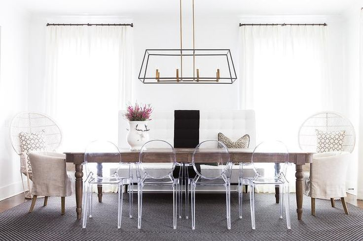 Alyssa Rosenheck - April Tomlison Designs - Chic dining room features a brass and iron linear chandelier illuminating an oval oak dining table lined with Ghost Chairs, black and white striped tufted dining banquette as well as linen slipcovered barrel back dining chairs placed at each end of the table.