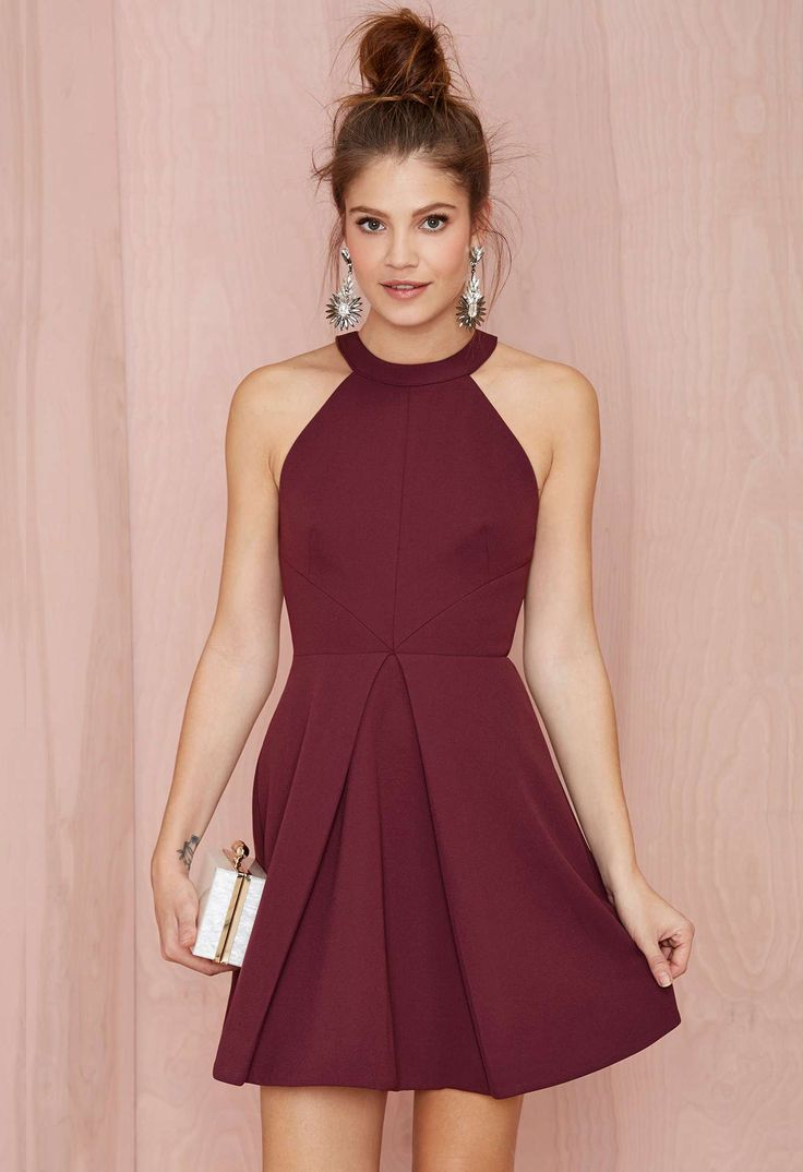 This structured burgundy dress has a cutaway neckline, pleating at skirt, cutout at back, and button/zip closures. Fully lined. You can match it with a faux fur jacket, high heels, and a metallic clutch.