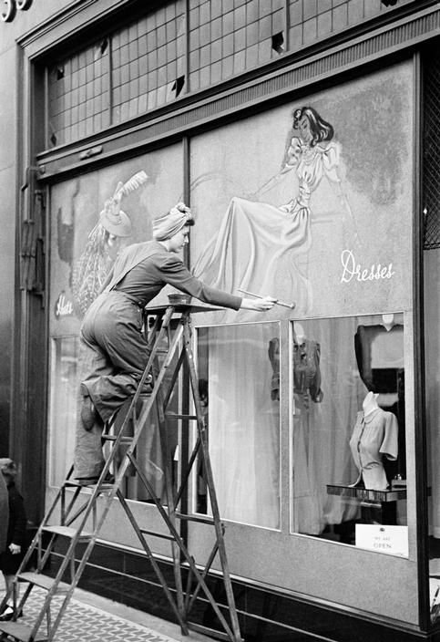 London, Oxford Street, World War II: The Blitz -  boarded up shop fronts are decorated with murals by student artists. 1940