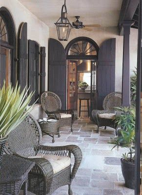 Grey flagstone floor, French doors with grey shutters and grey rattan furniture. Just lovely.