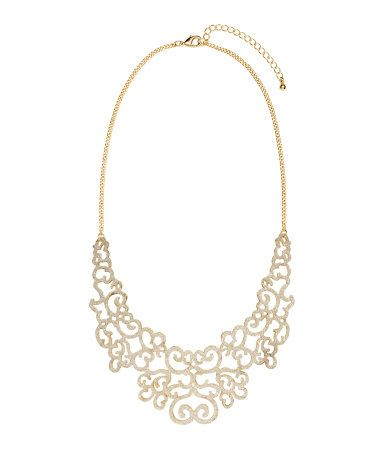 Short metal necklace. Rigid pendant with punched pattern and glittery front. Adjustable length, 17 1/4 - 20 1/2 in.