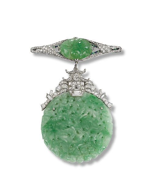 AN ART DECO JADE AND DIAMOND PENDENT BROOCH -  The surmount set with an oval-shaped carved jade plaque to the single-cut diamond surround with calibré-cut sapphire and emerald detail suspending a carved and pierced jade disc to the pavé-set diamond pagoda surmount, pendant asssociated, circa 1925