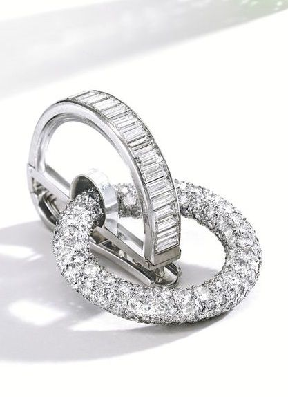 An Art Deco Platinum, Diamond and Rock Crystal Clip-Brooch, Cartier, France. The pavé-set ring surmounted by a diamond-set rock crystal hemisphere, set with baguette, round and single-cut diamonds, signed Cartier, Made in France, numbered, with workshop marks; circa 1930. #Cartier #ArtDeco #brooch