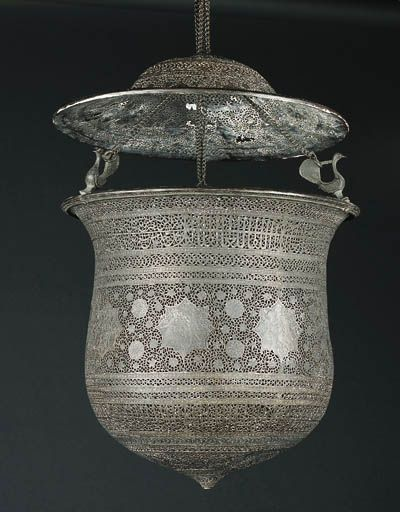 A QAJAR ENGRAVED AND PIERCED BRASS HANGING LAMP ISFAHAN, PERSIA, 19TH CENTURY Modelled after a European glass shape with large broad baluster body suspended on three chains attached to three birds, the chain passing through a recurved domes upper platter, the entire surface intricately worked with scrolling interlaced vine issuing palmettes around figural cartouches and roundels, between bands of similarly worked inscription cartouches and minor interlace bands, Base 12in. high