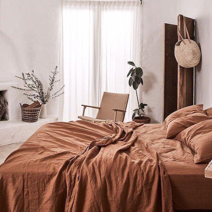 Rust terra-cotta bedding white walls minimalist boho bedroom decor with house pl