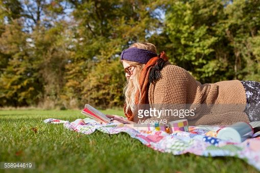 http://media.gettyimages.com/photos/side-view-of-young-woman-reading-novel-while-lying-on-picnic-blanket-picture-id558944619?s=170667a