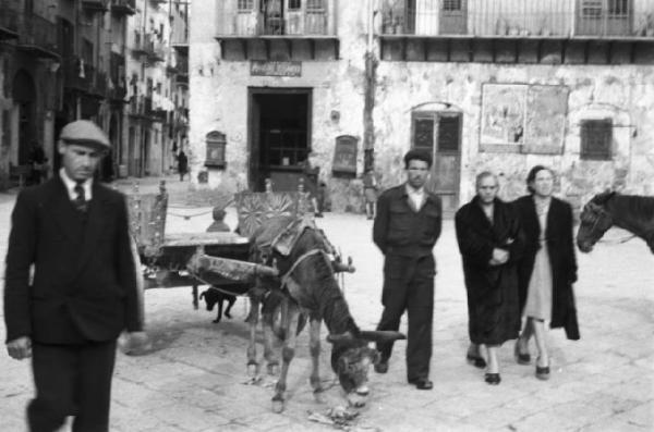 Italia Dopoguerra - Palermo - Un asino legato ad un carretto siciliano - Passanti