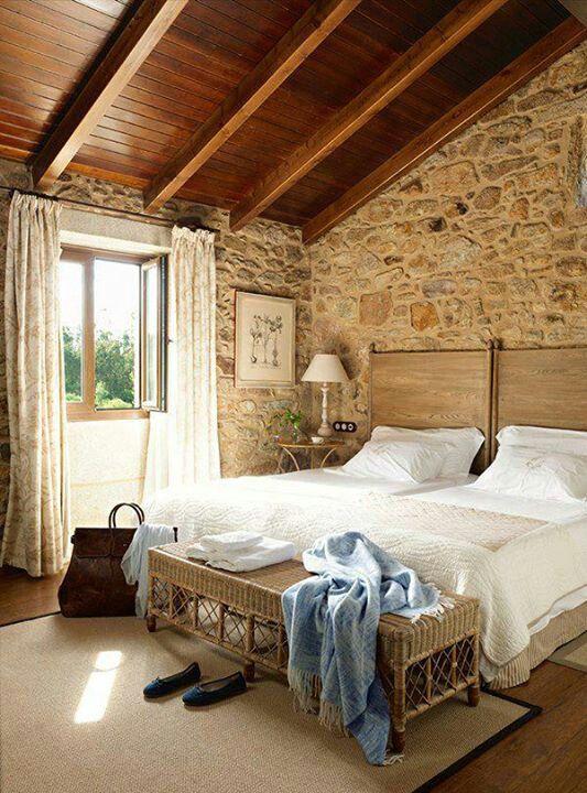 Bonito dormitorio con paredes de piedra y techo inclinado