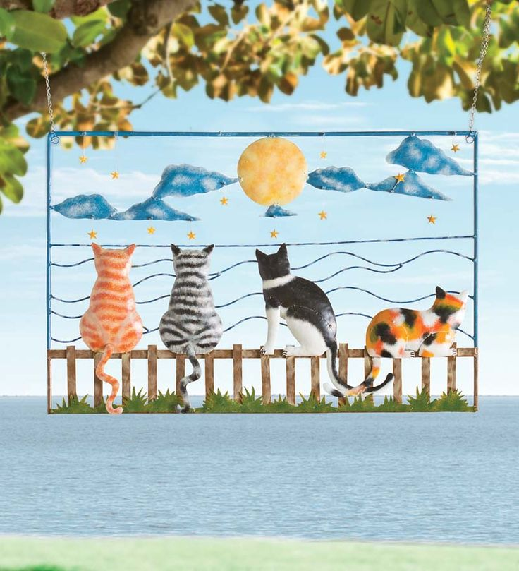 "Handcrafted Cats On A Fence Metal Wall Art; $100 • Handmade & hand painted by Bali artisans. • Features five colorful cats sitting on a fence watching the night sky. • The cats' tails & stars move & sway in the wind! • Whimsical wall art for any indoor or outdoor space. 30-1/2""L x 1-1/4""D x 20""H."
