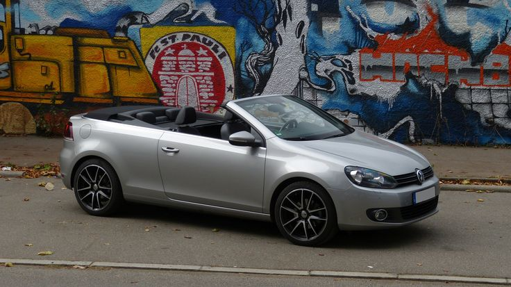 VW Golf VI Cabriolet in front of a wall painted with graffity
