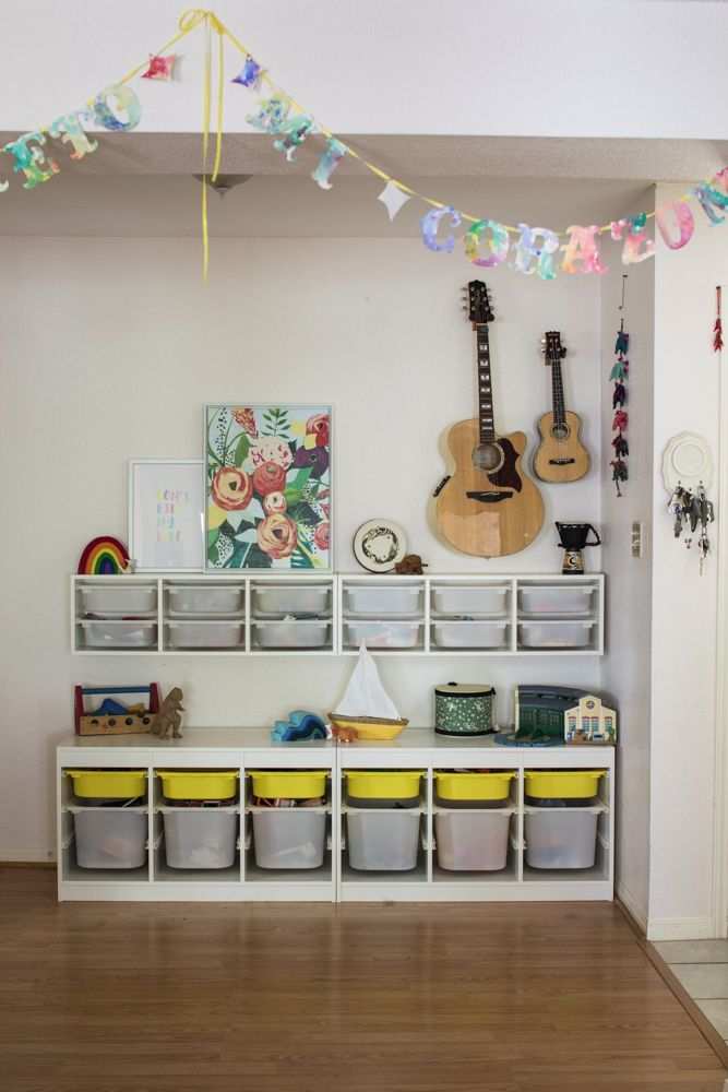 A former dining room turned storage area. Kids bins from Ikea, art prints, and guitars.