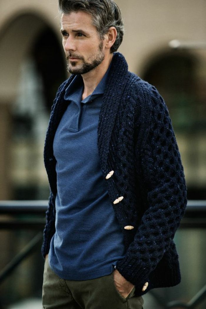 business casual outfits, older man with grayish hair, mustache and beard, wearing chunky-knit navy blue cardigan with white buttons, over blue shirt and khaki pants