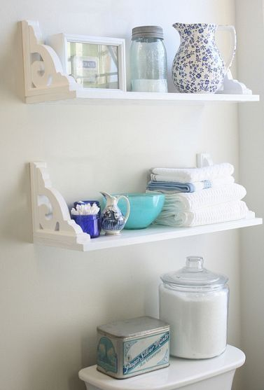 Great idea to hang the shelves upside down. The decorative brackets act like end caps. I love the decorative and functional blue containers paired with the white. Perfect!