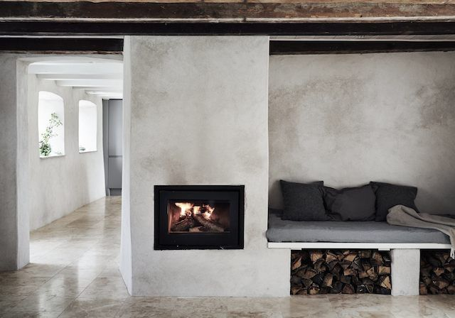Fireplace + cosy nook in a pared-back Swedish island retreat.