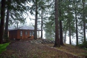 BEAUTIFUL OCEANFRONT ACRE & HOME – Powell River BC – Building your dream home or enjoy the well-built cabin with kitchen, 2 pc bathroom, woodstove, covered porch.  Large shop with 14x14 door. Bathroom building with wash, dryer & attached workshop. Power & water, all are cedar siding with metal roofing. Quiet area at the gateway to Desolation Sound where our mild weather allow for fishing, kayaking & exploring all year long. Pre-paid 999 year lease assures enjoyment for generations to come!