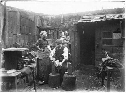 This photograph shows two home-workers, a man and a woman, making shovels by shaping scrap metal in their back yard in Bethnal Green. ca 1900.