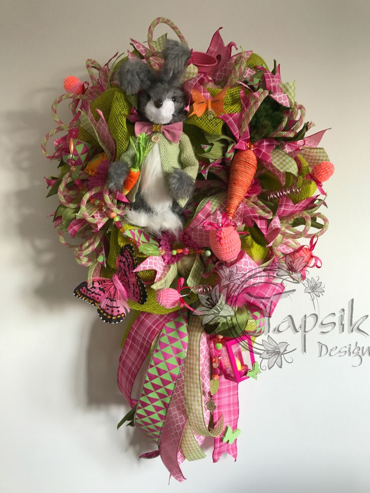 Easter Wreath or Spring Wreath. Base green burlap. Full with colorful ribbon strips a funky bow. One happy bunny, which was the inspiration for the creation of this wreath. Flowers, carrot, bird, small watering can, butterflies, handmade bead garland and LED lantern. And of course hand decorated eggs. Around up to 50 cm but with the ribbon - the lenght is up to 80 cm. I must say, this wreath is one of my favorits.
