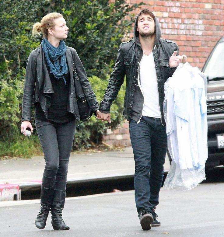 Revenge's Emily VanCamp and Joshua Bowman holding hands.