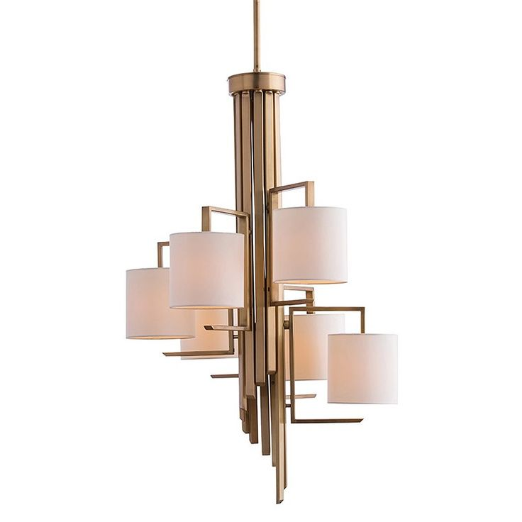 """Cascading flat iron rods finished in antique brass form the cylindrical base of this graphic chandelier. Six lights descend in a stair step fashion each topped with an ivory microfiber shade.   Materials: Steel Finish: Antique Brass Shade: Ivory Microfiber Round Drum Shade Dimensions: 6""""W Top x 6""""W Bottom x 6""""H"""