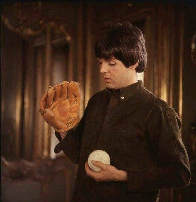 Beatle Paul McCartney looks a tiny bit confused by his ball and glove!