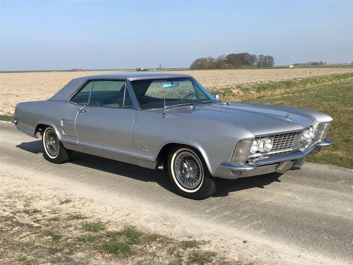 Deze steeds populair wordende Buick Riviera uit 1964 is een aantal maanden terug helemaal uit elkaar gehaald, ook de motor en transmissie zijn uit de auto gehaald. Vervolgens kaal gehaald, gespoten en weer opgebouwd.  De grijze/zilveren metallic lak ziet er dan ook prachtig uit, ook het chroom verkeert in goede staat.   De 'matching numbers' 465 Wildcat motor, 425ci V8, loopt netjes rond en levert 340 pk. Ook de automatische transmissie schakelt soepeltjes.  De bodem is hard en e...