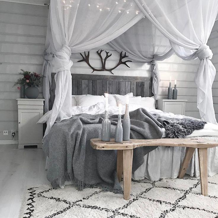 Tiulowy baldachim oraz czarne poroże nad łóżkiem w sypialni