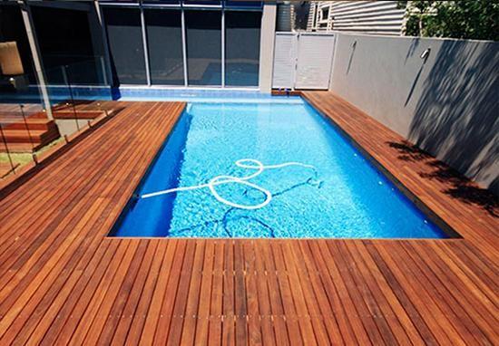 Deck de madeira em volta de piscina, feito pela Mad Telhas.