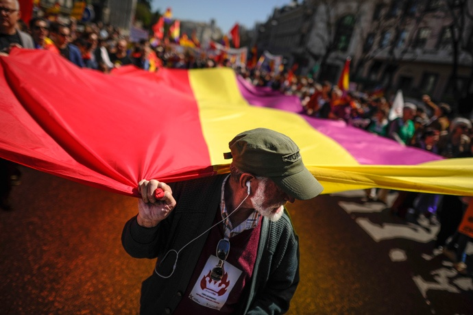 People hold a giant flag of Spain's second Republic during a demonstration by Republicans in Madrid, on April 14, 2013 to commemorate the 82nd anniversary of the Second Republic (AFP Photo / Pedro Armestre)