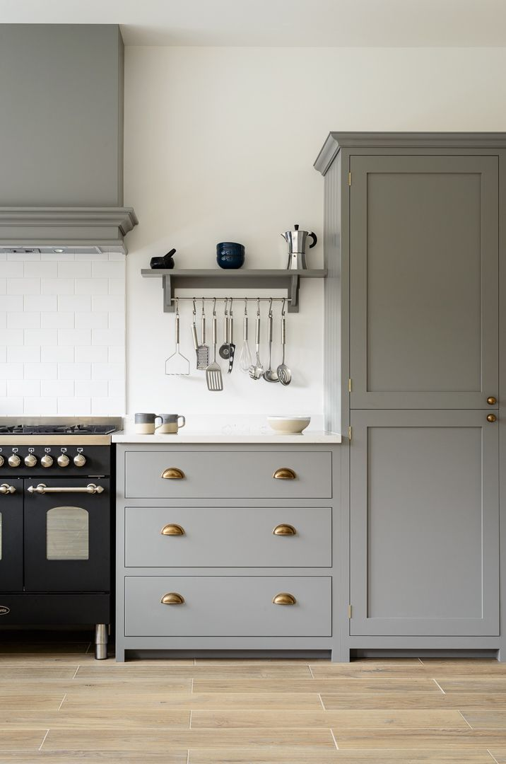 Beautiful deVOL Shaker cabinets painted in 'Lead', classic brass door furniture, a lovely black Britannia range cooker and beautiful Aged Oak Porcelain flooring by our sister company @floorsofstone
