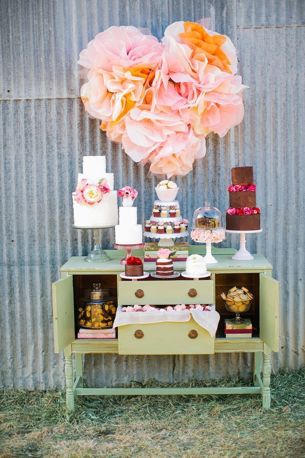 Rustic outdoor wedding dessert table with different cakes on top plus a lovely ruffled heart backdrop