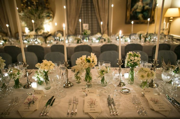 Up close-----so simple, with small bouquets of white blooms, silver candlesticks and long white tapers