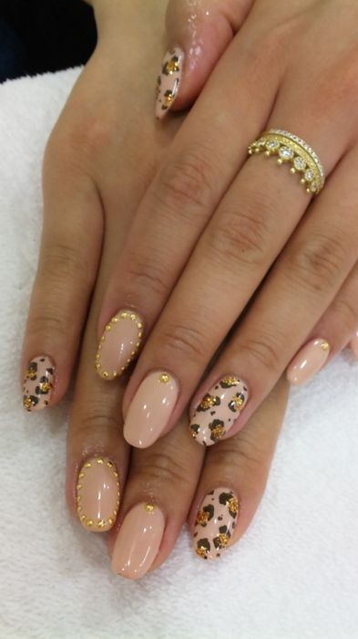 Nude leopard print gold glitter and studded nails.