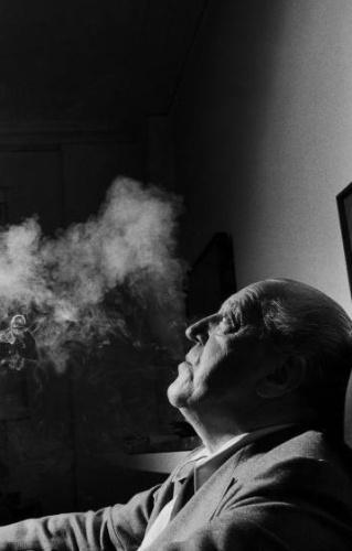 """O arquiteto Mies van der Rohe fuma ao ser fotografado em 1956, em Nova York. Nascido em Aachen com o nome de Maria Ludwig Michael Mies, o alemão completaria 126 anos em 2012. Considerado um dos mestres da arquitetura moderna, Mies van der Rohe declarou, em 1958, à publicação """"Baukunst und Werkform"""": """"Procuro fazer dos meus edíficios cornijas neutrais, em que os homens e as obras de arte possam conduzir uma vida autônoma. Para fazer isso é necessária uma atitude respeitosa diante das coisas"""""""