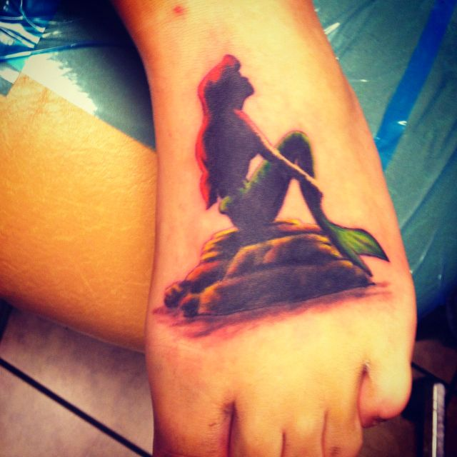 The Little Mermaid silhouette tattoo.... Not sure on the color?? And i would want a smaller one.