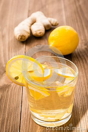 Lemonade with lemon and ginger in a transparent glass on a wooden table