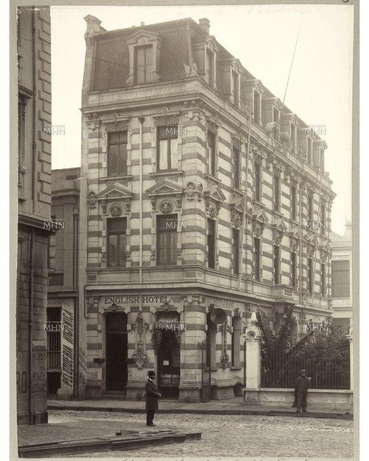 Vista lateral del antiguo Hotel Inglés, conocido actualmente como Hotel Reina Victoria, que enfrenta la Plaza Sotomayor de Valparaíso, construido por Esteban Harrington en 1902. Escrito en la muralla, se aprecia un anuncio de la Peluquería Higiénica. Región de Valparaíso. - Fecha Fotog.: 1910 --- M.H.N.