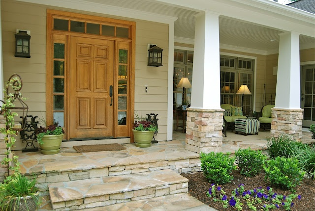 Welcoming front porch - stonework adds character, color and warmth. Low-maintenance landscape, Craftsman light fixtures stone porch, columns. Get the look with a traditional Clopay fiberglass entry door or play out the Craftsman theme with a Craftsman Collection fiberglass entry door instead.