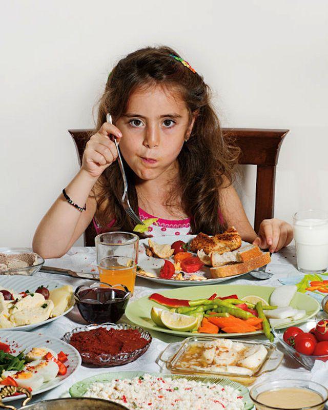 """Doga Dunce, 8 años, Estambul. Su desayuno incluye miel y nata en pan tostado, huevos fritos con una salchicha picante llamada """"sucuk"""", mantequilla, huevos duros, jarabe de uva, quesos de vaca, cabra y borrego, pan, jitomate, pepino, leche y jugo de naranja (nada maaaas)."""